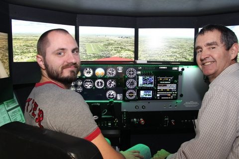 Student and teacher posing in a flight simulator