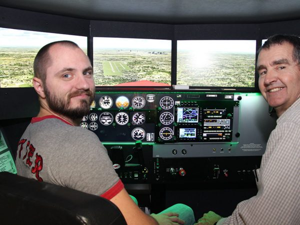 Student and teacher posing in a flight simulator