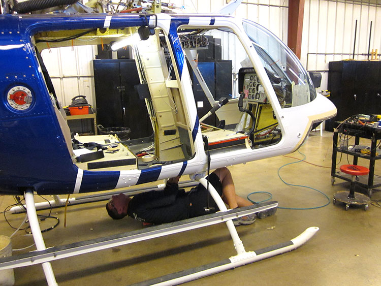 Man inspecting the bottom of a helicopter