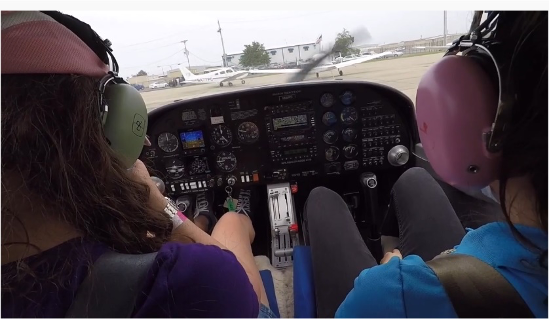 Two people sitting in the cockpit of a plane