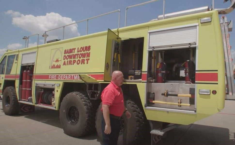 Airport employee Terry standing by a fire truck