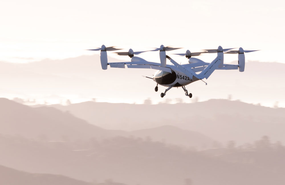 An air taxi in flight with hills in the background
